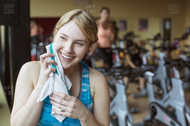 Smiling woman wiping sweat while standing in gym