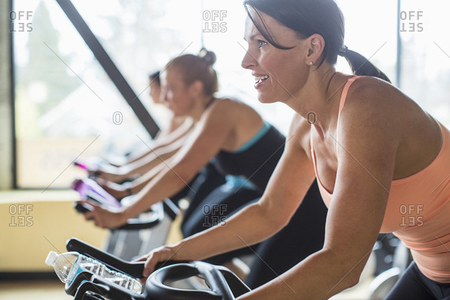 Smiling women cycling on exercise bikes at health club