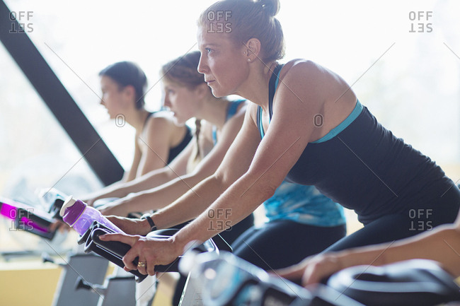 Women cycling on exercise bikes at health club
