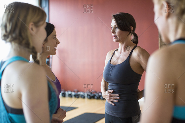Female friends talking while standing in health club