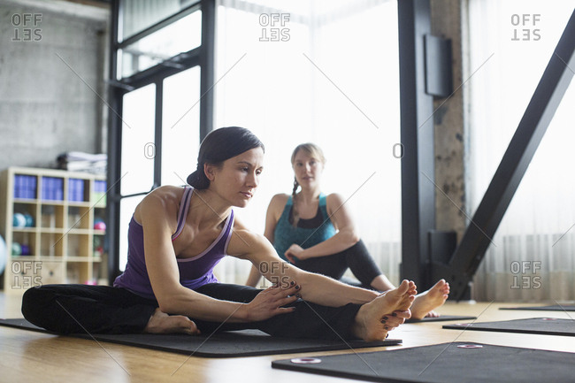 Women exercising on exercise mats in gym