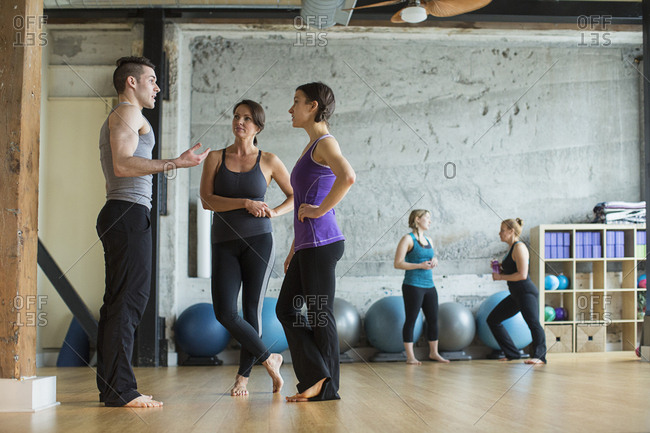 Male instructor guiding women in gym
