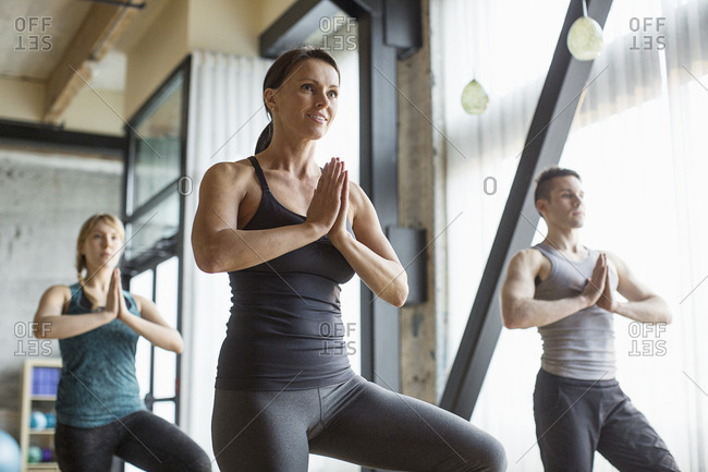Male instructor with women practicing tree pose in gym