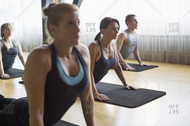 Women with male instructor practicing upward facing dog position in gym