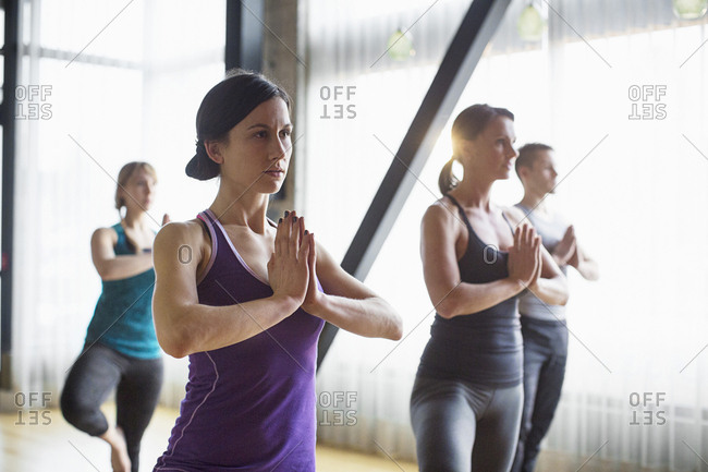 Male instructor with women practicing tree pose in health club