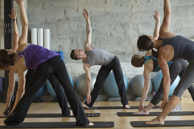 Male instructor guiding women in doing triangle position in gym