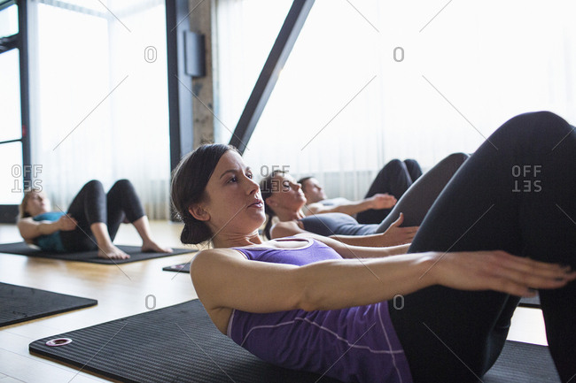 Male instructor with women exercising while lying on exercise mats in gym