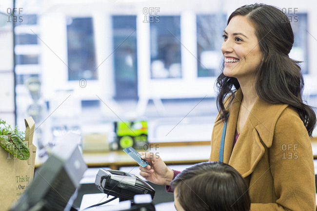 Smiling woman holding credit card while standing with son at supermarket