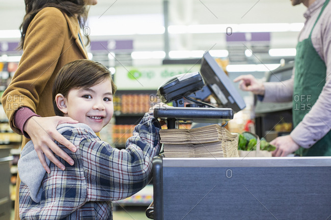 Portrait of boy standing with mother standing counter at supermarket