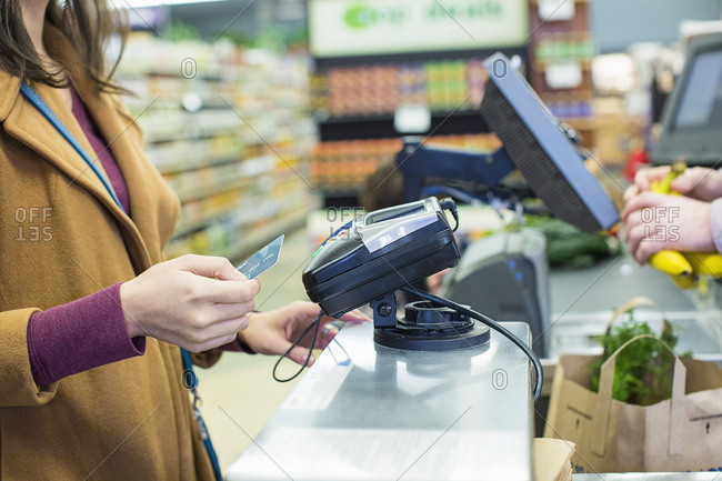 Midsection of woman paying bill with credit card while standing by counter at supermarket
