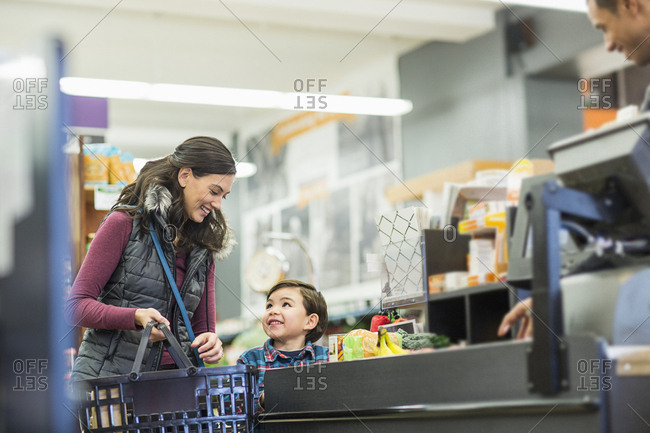 Smiling woman holding basket while standing with son by checkout counter at supermarket