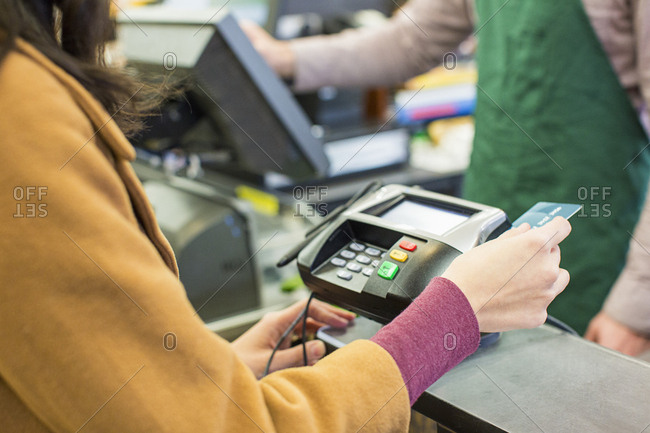 Midsection of woman paying bill with credit card at supermarket
