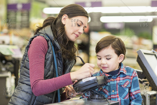Mother with son at checkout counter in supermarket