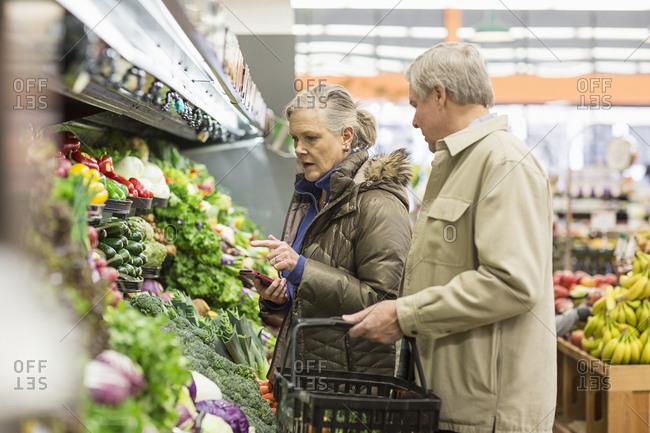 Senior couple shopping for vegetables at supermarket