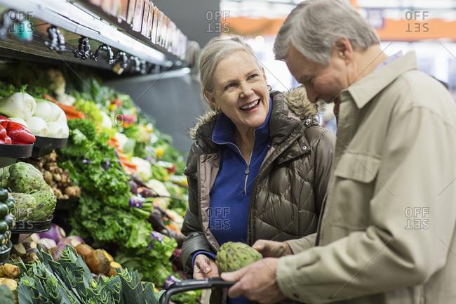 Smiling senior couple shopping for vegetables at supermarket
