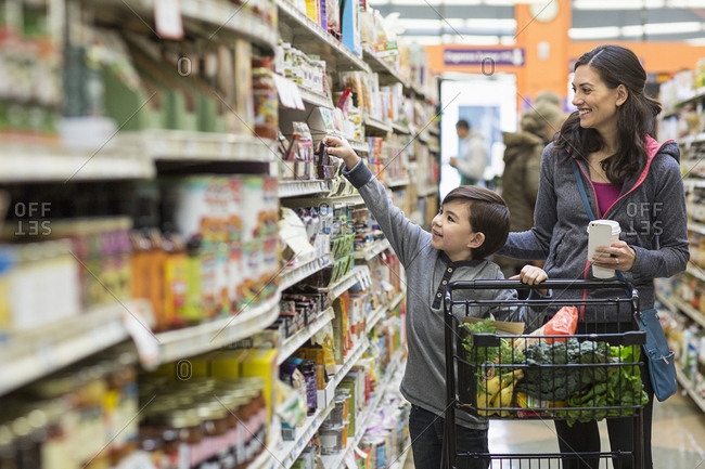 Boy shopping with mother in supermarket