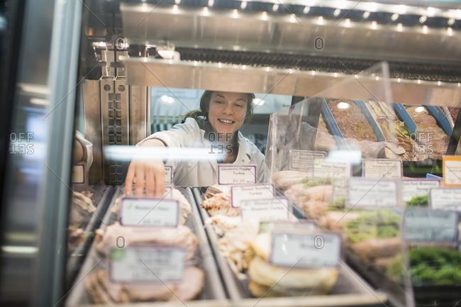 Female worker arranging food in display cabinet at supermarket