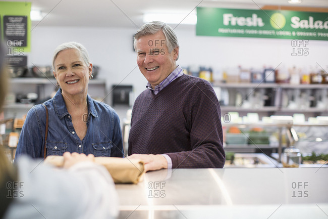 Cropped image of woman giving packet to senior couple at supermarket