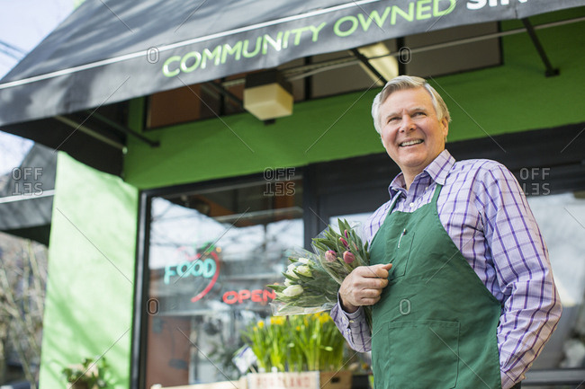 Senior male florist standing against flower shop