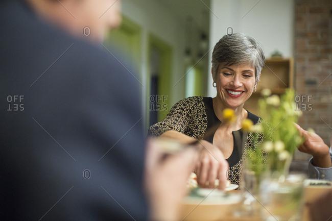 Smiling woman at table during social gathering