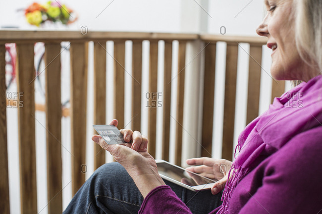 Close-up of woman looking at credit card while using tablet computer