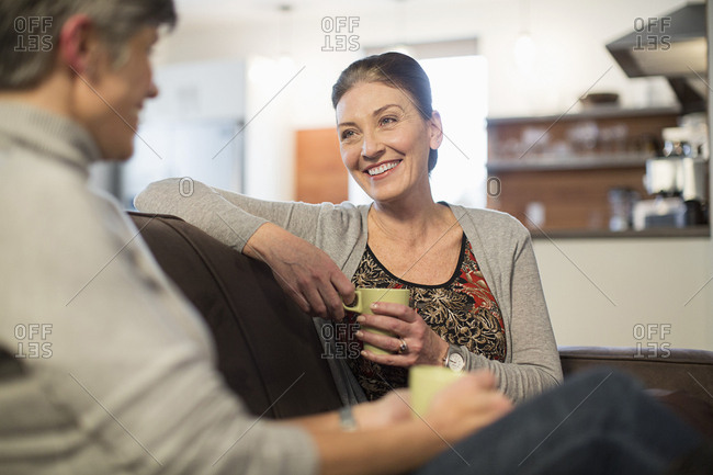 Smiling female friends talking while sitting on sofa at home