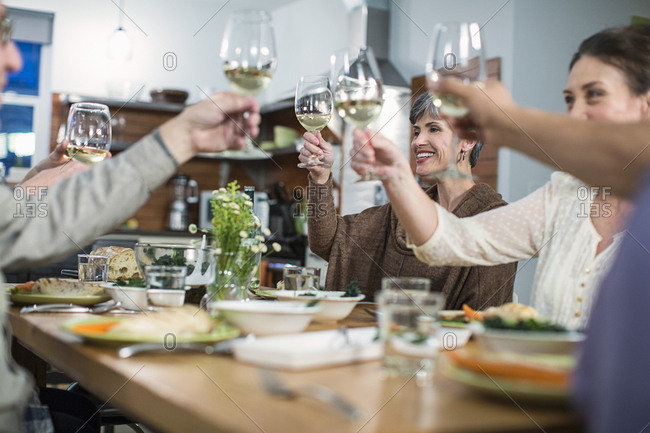 Happy friends toasting wine while sitting at table during social gathering