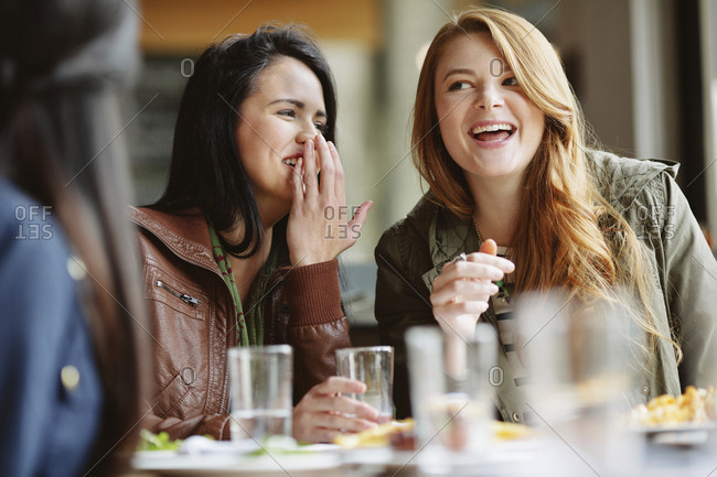 Happy woman whispering into friend's ear at table in restaurant
