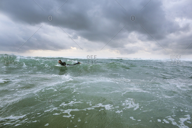 Man surfing on sea against cloudy sky