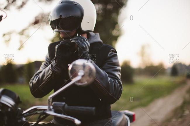 Male biker adjusting helmet while sitting on motorcycle