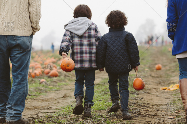 Low section of parents with sons walking on pumpkin patch during foggy weather
