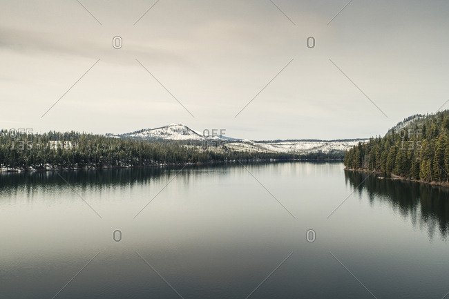 Scenic view of calm river against sky during winter