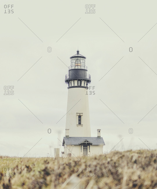 Surface level of lighthouse on field against sky