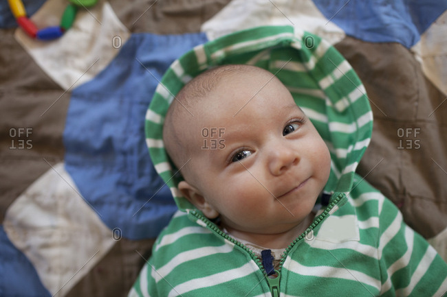 High angle portrait of cute baby boy wearing hooded shirt while lying on bed at home