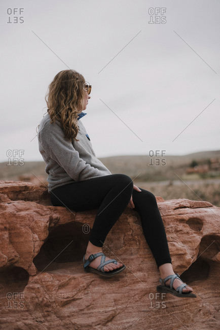 Full length of woman sitting on rocks against sky at Red Rock Canyon National Conservation Area