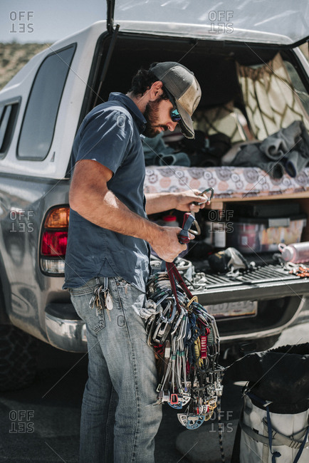 Side view of male hiker holding climbing equipment while standing by off-road vehicle