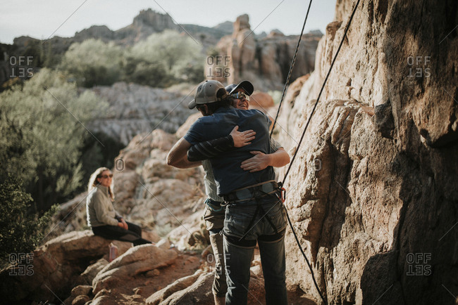 Woman looking at male friends embracing on rock formation at Red Rock Canyon National Conservation Area