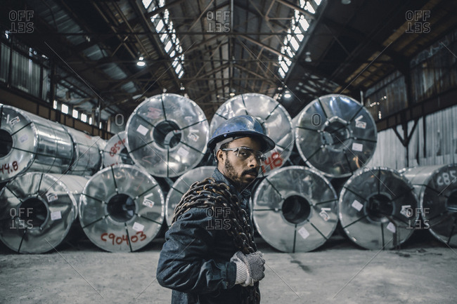 Portrait of male worker carrying chain while standing against rolled up steel sheets at factory