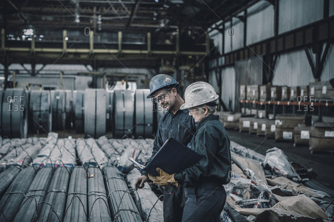 Coworkers discussing documents while walking in metal industry