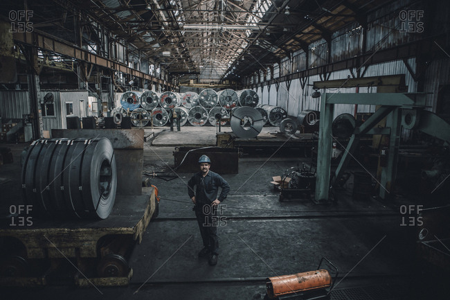 High angle view of male worker standing against steel sheets in factory