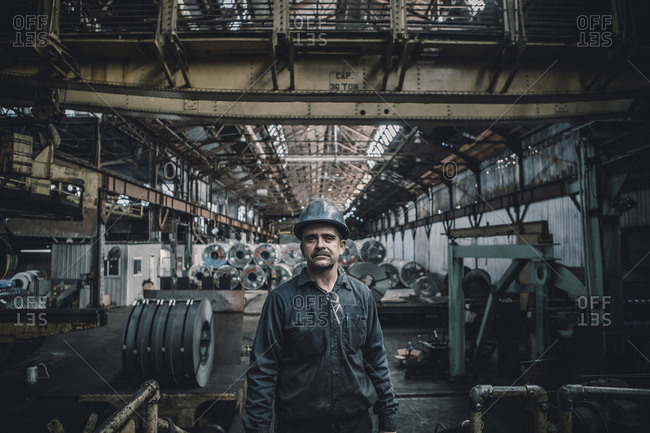 Portrait of confident male worker standing against steel sheets in factory
