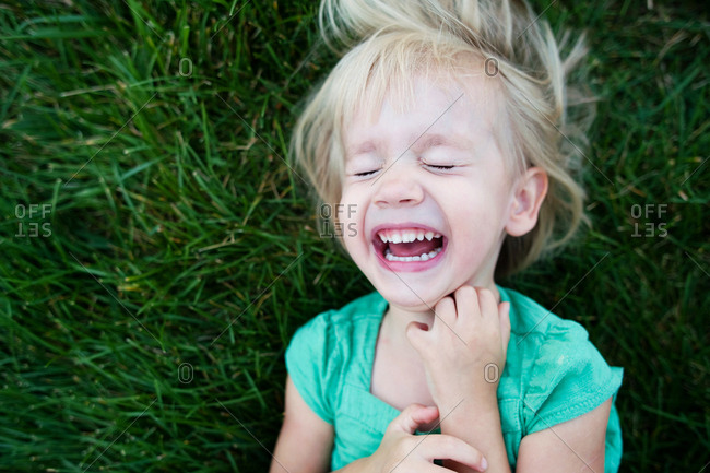 Overhead view of girl crying while lying on grassy field at park
