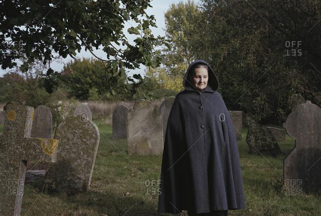 Sad woman wearing coat walking on field in graveyard