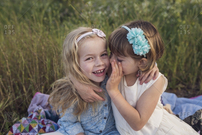 High angle view of girl whispering in sister's ear while sitting on blanket in park