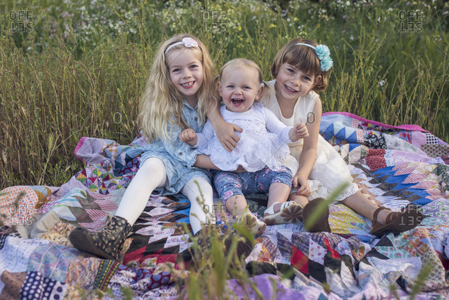 Portrait of happy sisters sitting on blanket in park