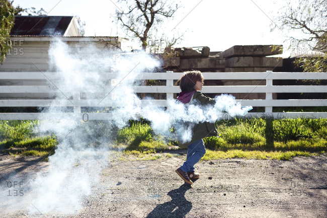 Playful boy holding distress flare while walking in backyard