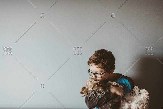 Boy kissing Yorkshire Terrier against wall at home