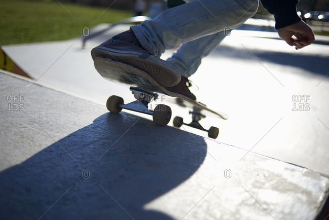 Low section of girl skateboarding on sports ramp at park
