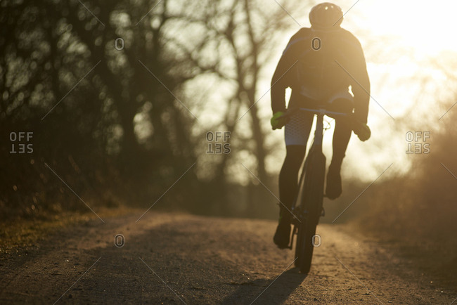 Silhouette woman riding bicycle on footpath against sky during sunset