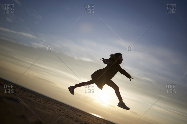 Happy girl jumping at beach against sky during sunset